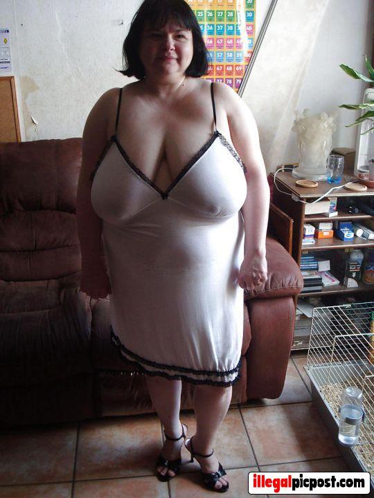 Dikke huisvrouw staat in haar nachthemd