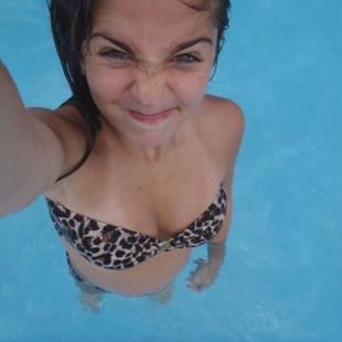 Meisje trekt gekke bek als ze selfie maakt in het zwembad